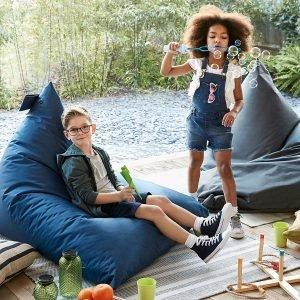 Kids playing outdoors with large blue beanbags