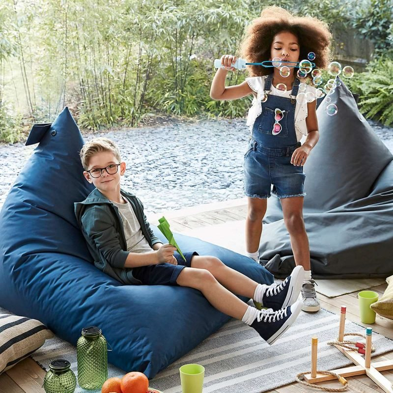 Kids playing outdoors with large blue bean bags
