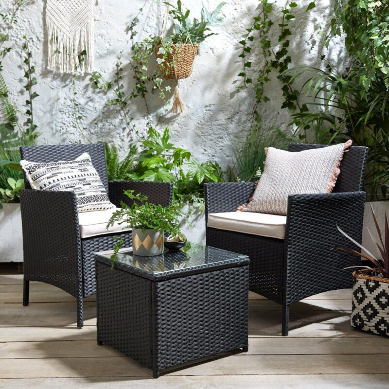 Black rattan garden chairs with a matching table