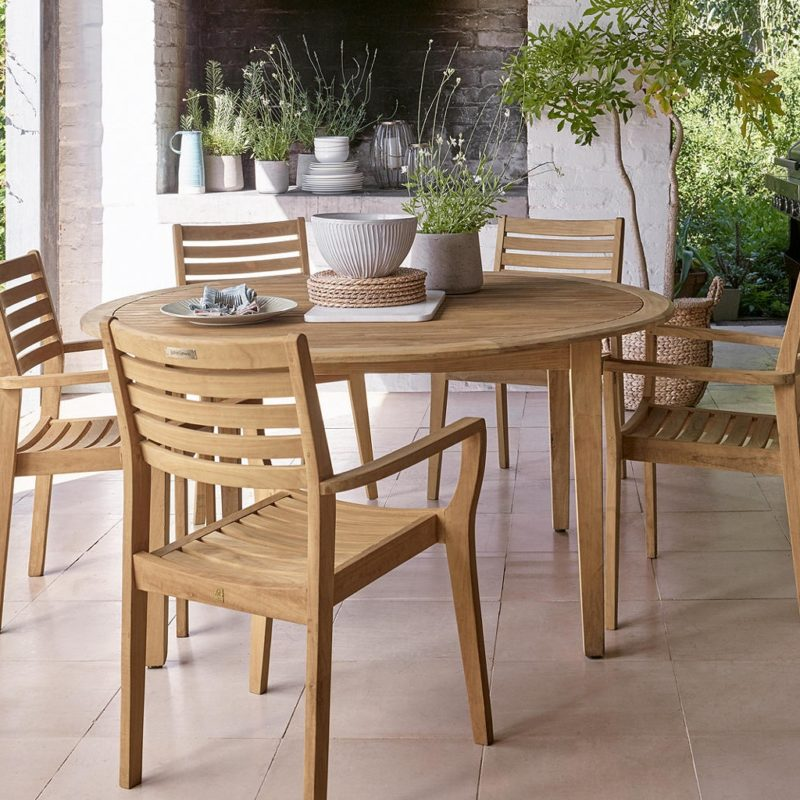 Round teak garden dining table and four matching chairs