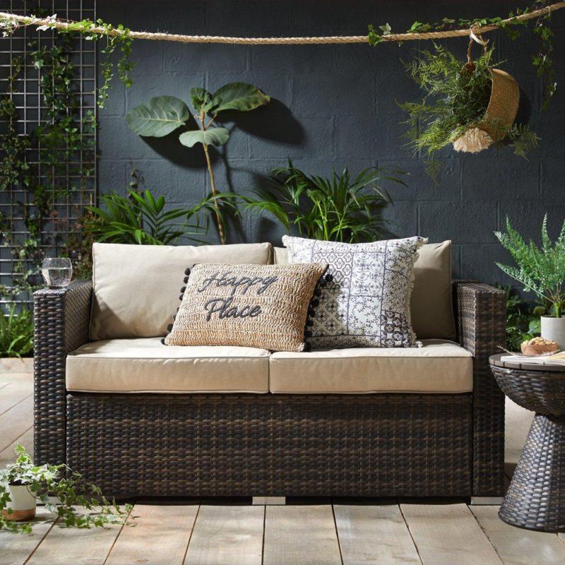2-seater rattan sofa with cream coloured cushions
