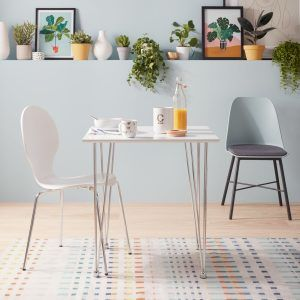 White dining table with tri-pod legs