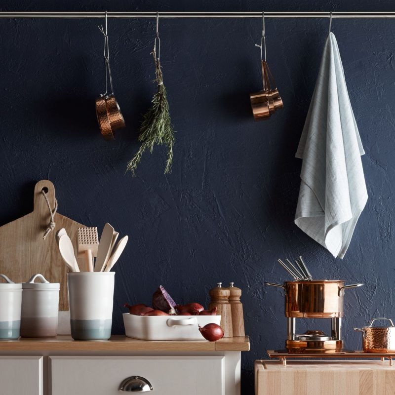 Copper accessories in a dark blue painted kitchen