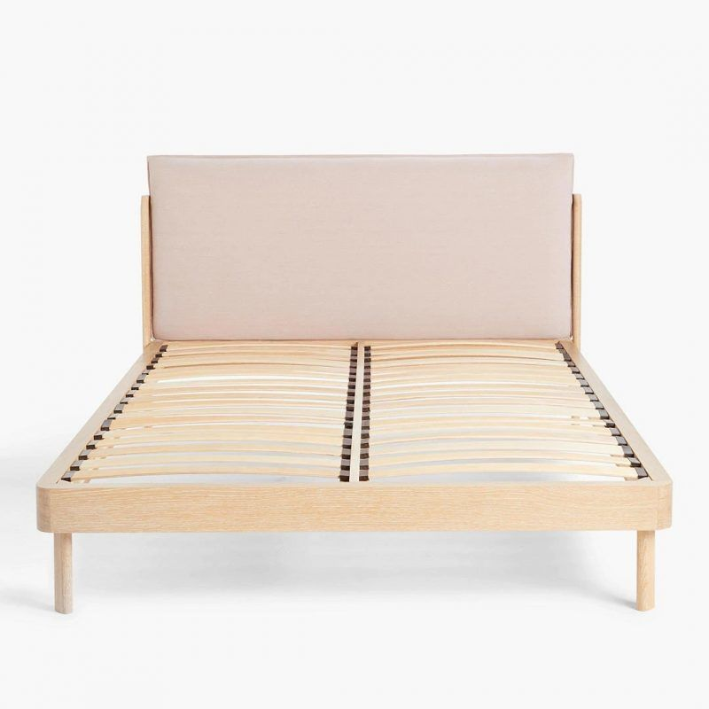Oak bed frame with curved edges and large pink headboard