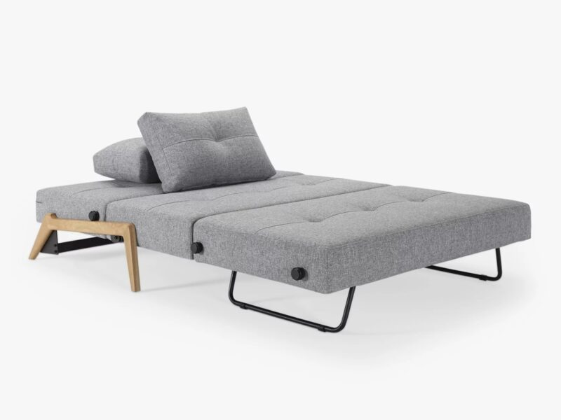 Grey fabric sofa bed laid flat with cushions
