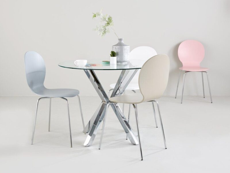 Glass-topped dining table with polished metal chopstick-style base