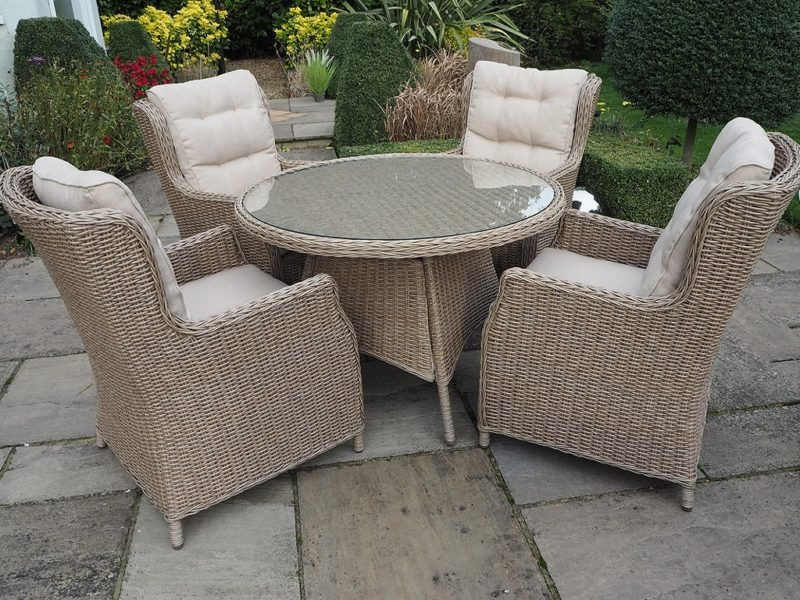 4 rattan chairs and a glass topped rattan dining table