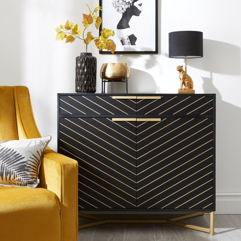 Black-painted 2-door sideboard with gold coloured handles, gold chevron pattern finish and gold-painted metal legs