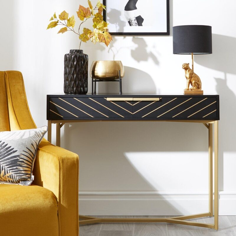 Black console table with gold pattern and gold legs