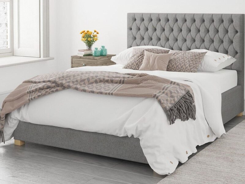 Grey fabric bed frame with buttoned headboard and storage base