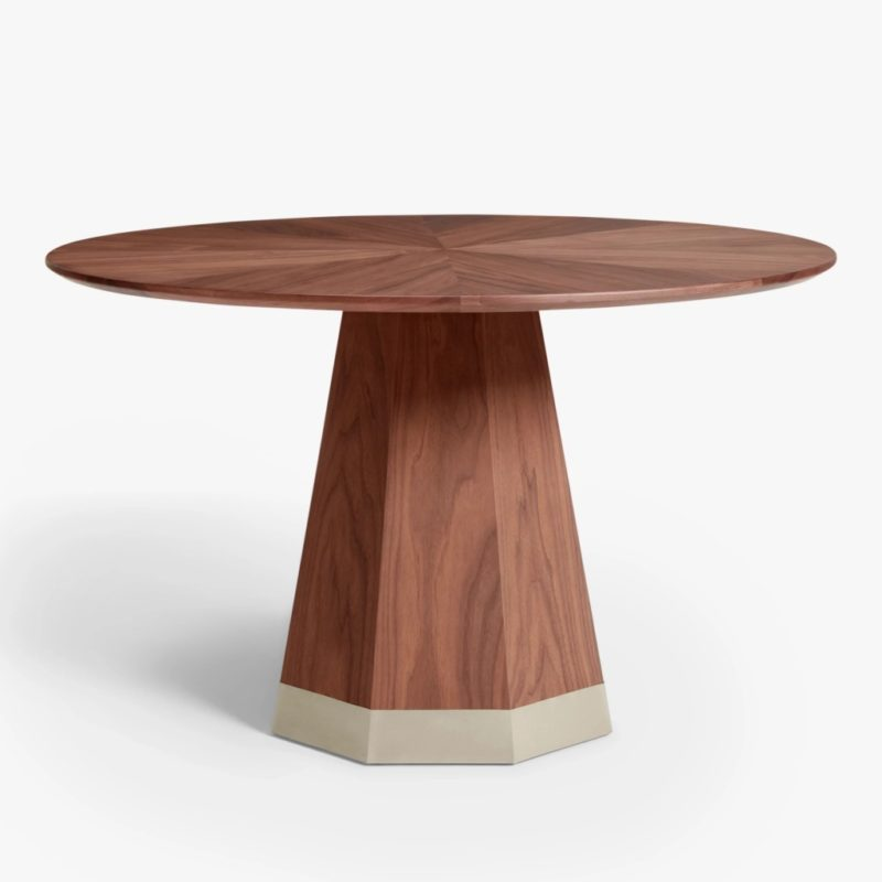 Round walnut dining table with geometric-shaped base