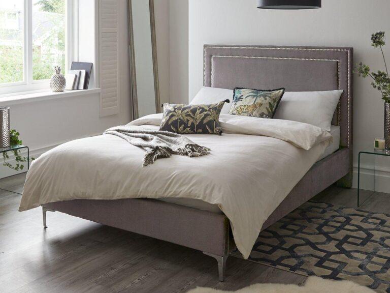 Grey velvet upholstered bed frame with stud detail headboard