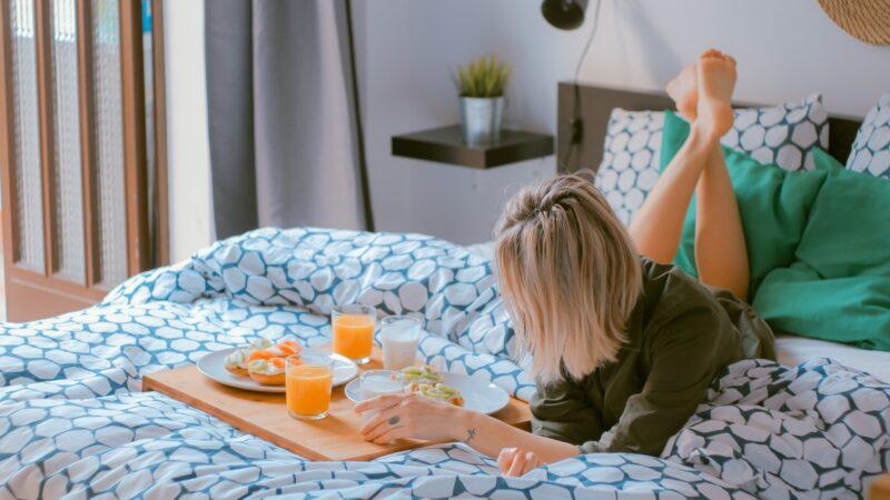 Woman enjoying breakfast on bed