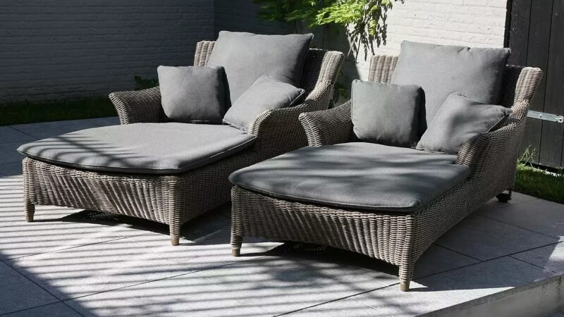 Pair of wicker sun loungers with grey cushions