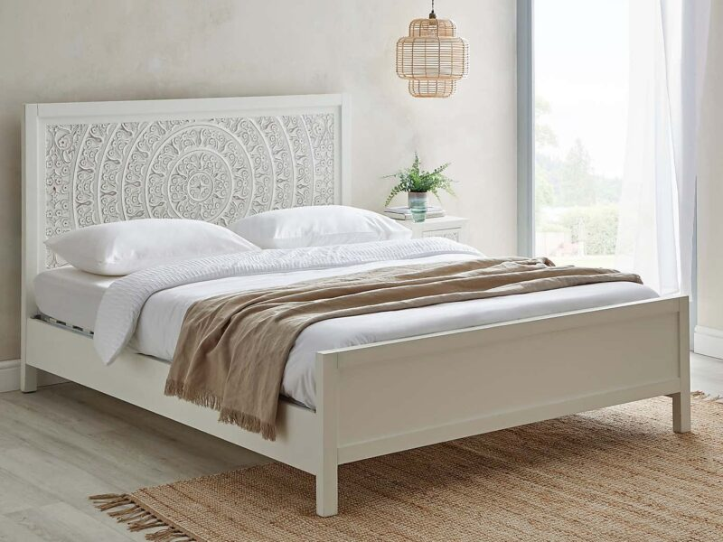 White wooden bed frame with large carved headboard